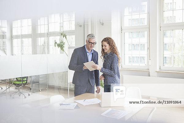 Geschäftsmann und Frau im Sitzungssaal mit Tablette