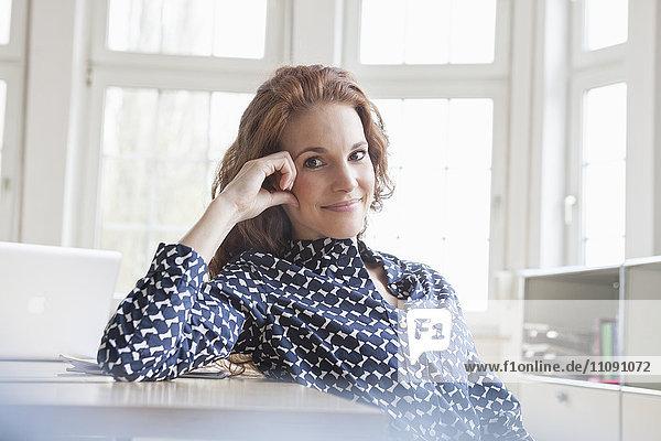 Porträt einer lächelnden Frau am Schreibtisch im Büro