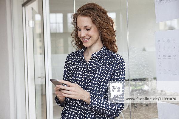 Lächelnde Frau im Büro mit Blick auf das Handy