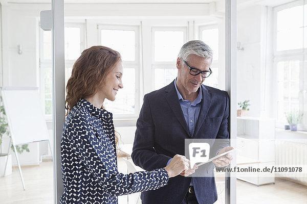 Geschäftsmann und Frau im Büro mit Tablette