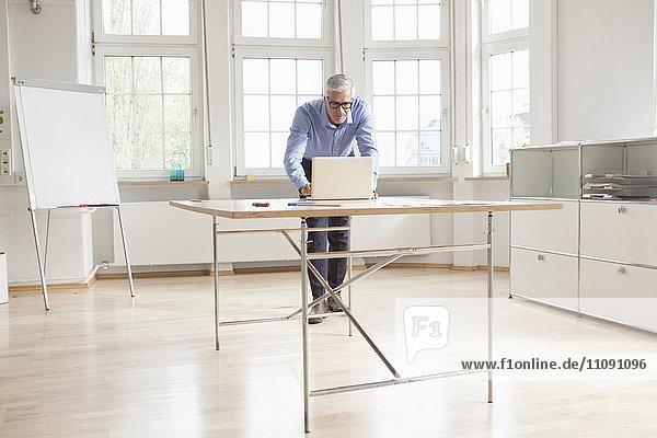 Ausgereifter Geschäftsmann mit Laptop im hellen Büro