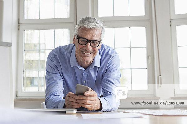 Porträt eines lächelnden reifen Geschäftsmannes am Schreibtisch mit Handy