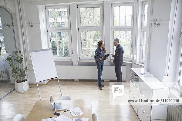 Geschäftsmann und Frau im Sitzungssaal im Gespräch