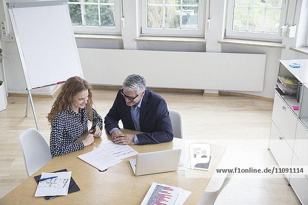 Geschäftsmann und Frau sitzen am Vorstandstisch und schauen sich Dokumente an.