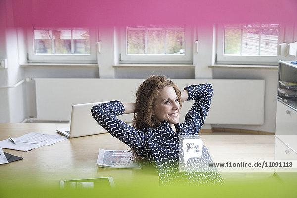 Lächelnde Frau im Büro lehnt sich zurück