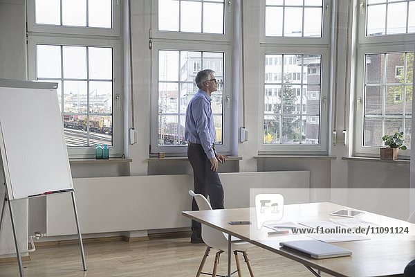 Ein reifer Geschäftsmann  der im Büro steht und aus dem Fenster schaut.