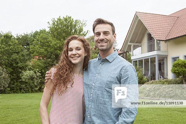 Porträt eines lächelnden Paares im Garten