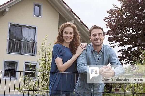 Porträt eines lächelnden Paares am Gartenzaun vor dem Haus