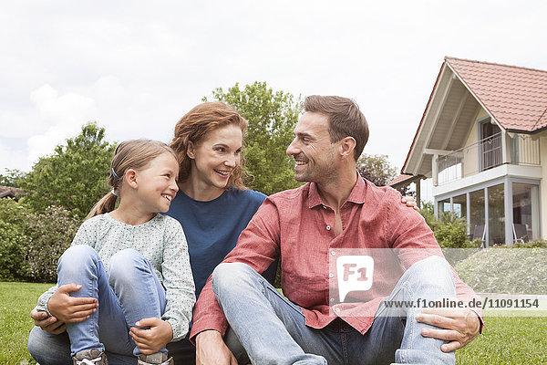 Lächelnde Familie sitzend im Garten
