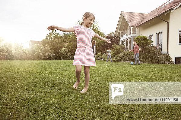 Mädchen tanzen im Garten mit Familie im Hintergrund
