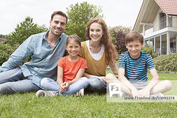 Portrait of smiling family sitting in garden