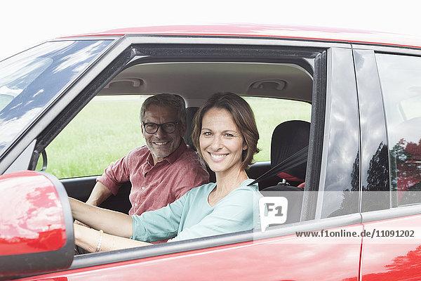 Porträt eines glücklichen reifen Paares im Auto