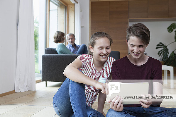 Lächelnde Teenager-Geschwister teilen sich die Tablette im Wohnzimmer mit den Eltern im Hintergrund.