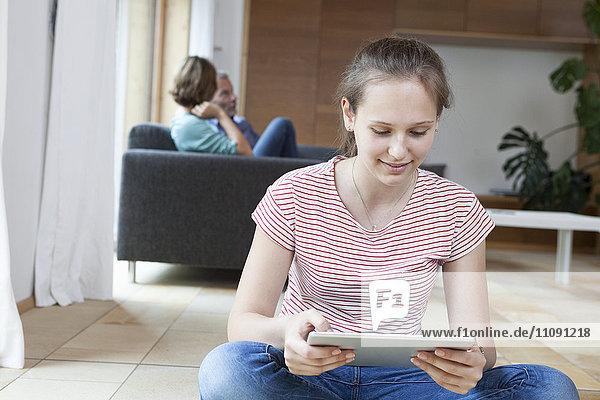 Lächelndes Mädchen mit Tablette im Wohnzimmer mit Eltern im Hintergrund