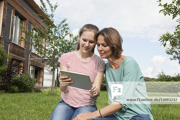Mother and daughter sharing digital tablet in garden