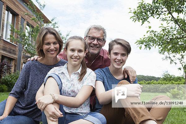 Portrait of happy family sitting in garden