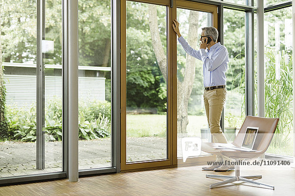 Ein Mann am Telefon steht in seinem Wohnzimmer und schaut durchs Fenster.