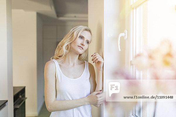 Blonde Frau zu Hause aus dem Fenster schauend