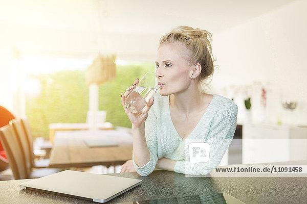 Frau in der Küche trinkt Wasserglas