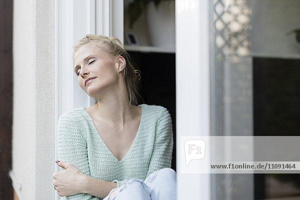 Blonde Frau entspannt an der Terrassentür