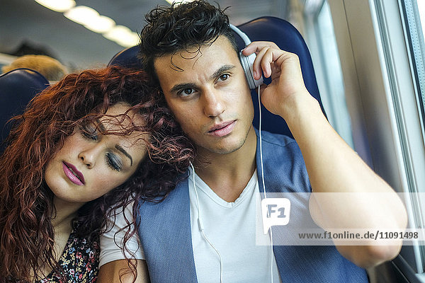 Portrait of relaxed young couple in a train