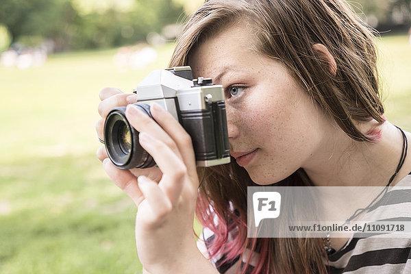 Junge Frau beim Fotografieren im Park