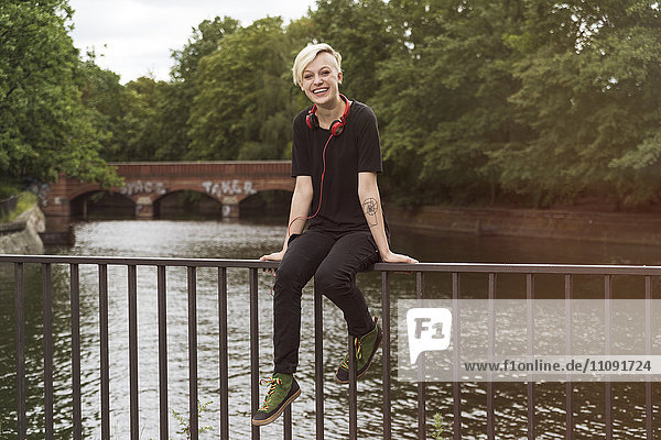 Laughing young woman sitting on railing in front of a canal