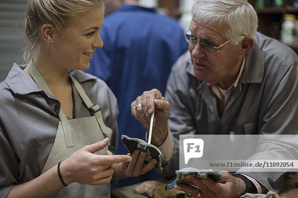 Ausbilder im Gespräch mit dem Auszubildenden in der Werkstatt mit Bronzegussteil