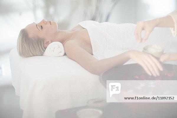 Junge Frau liegt auf dem Massagetisch und taucht ihre Hand in Rosenwasser.