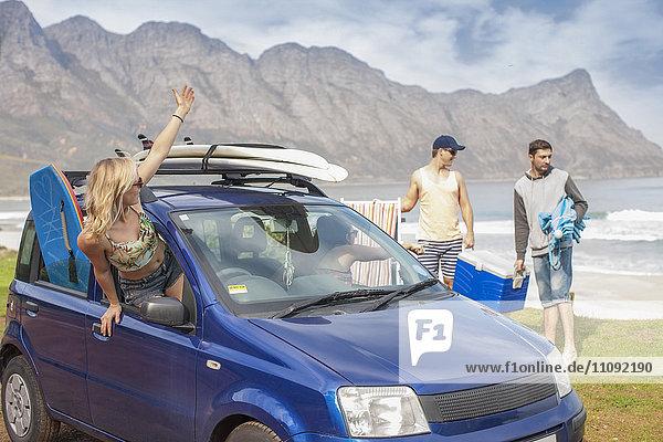 Freunde mit Surfbrettern im Auto an der Küste