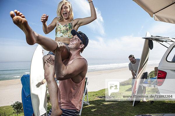 Mann hebt aufgeregte Frau an der Küste hoch