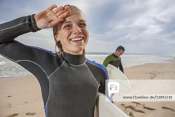 Lächelnde junge Frau mit Surfbrett am Strand