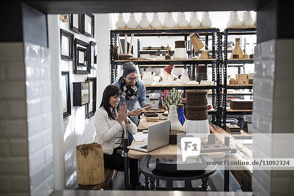 Mann und lächelnde Frau betrachten Laptop im Geschäft mit Regal im Hintergrund
