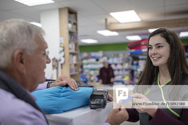 Senior man at counter paying with credit card