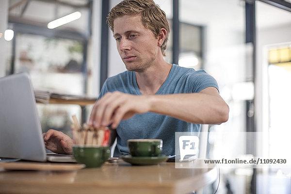 Junger Mann mit Laptop in einem Café
