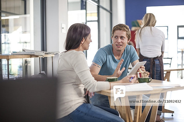 Mann und Frau sprechen in einem Cafe mit digitalem Tablett