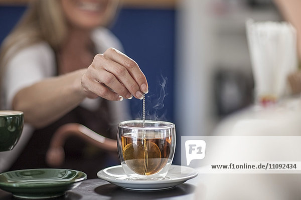 Woman in a cafe preparing glass of tea
