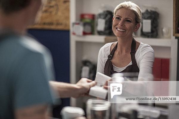 Frau im Café bei der Übergabe der Quittung an den Kunden