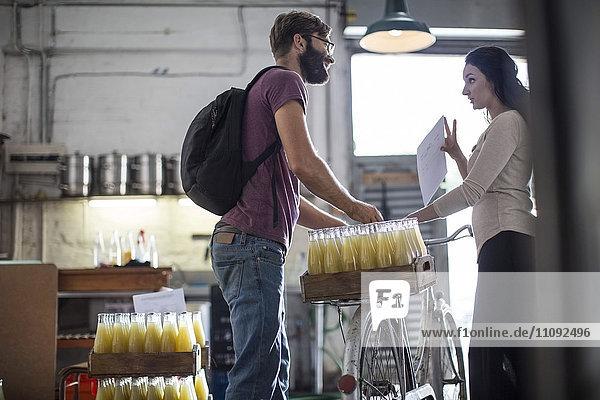 Auslieferer mit Saftflaschen auf dem Fahrrad im Gespräch mit der Frau im Lagerhaus