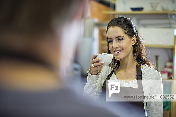 Smiling woman drinking coffee from cup looking at man