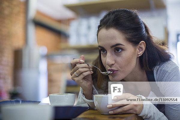 Junge Frau schmeckt Kaffee