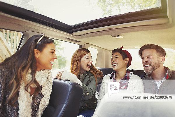 Paare fahren und lachen im Auto