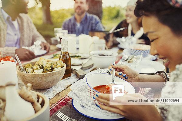 Lächelnde Frau isst Suppe am Terrassentisch mit Freunden