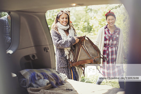 Lächelnde Frau  die den Rucksack in den Kofferraum des Autos lädt.