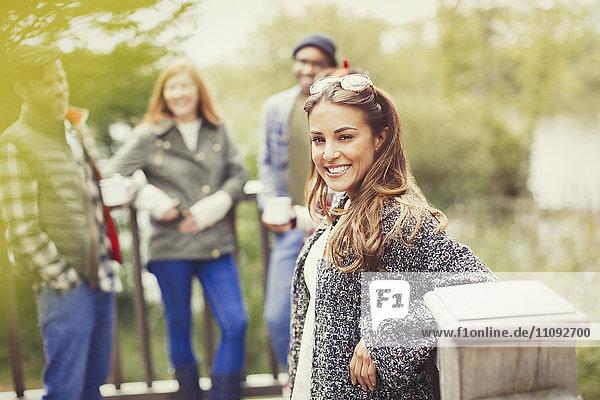 Portrait lächelnde Frau mit Freunden auf dem Balkon