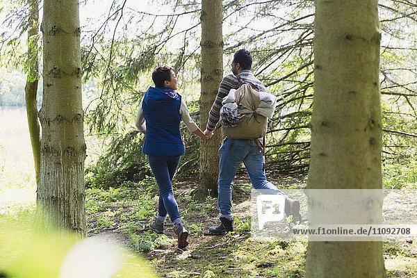 Paar beim Händchenhalten und Wandern mit Rucksack im Wald