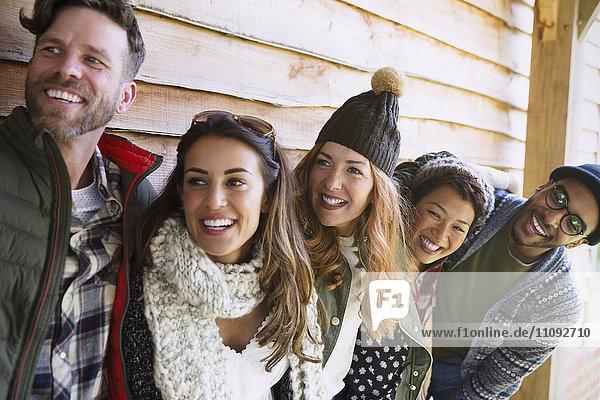 Lächelnde Freunde stehen in einer Reihe vor der Kabine.