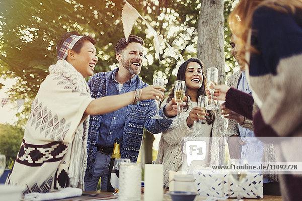 Freunde toasten Champagnergläser auf der Terrasse