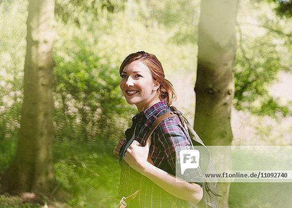 Lächelnde Frau mit Rucksackwandern im sonnigen Wald