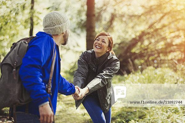 Lächelndes Paar hält Hände beim Wandern im Wald